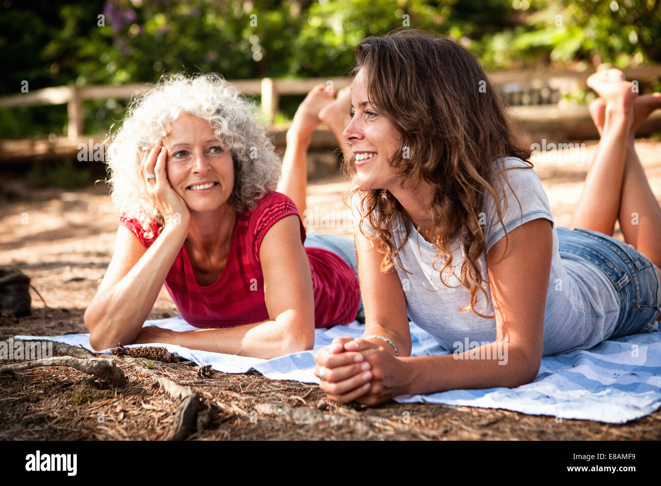 Mother and daughter on picnic blanket by the Blue Pool, Wareham, Dorset, United Kingdom - Stock Image