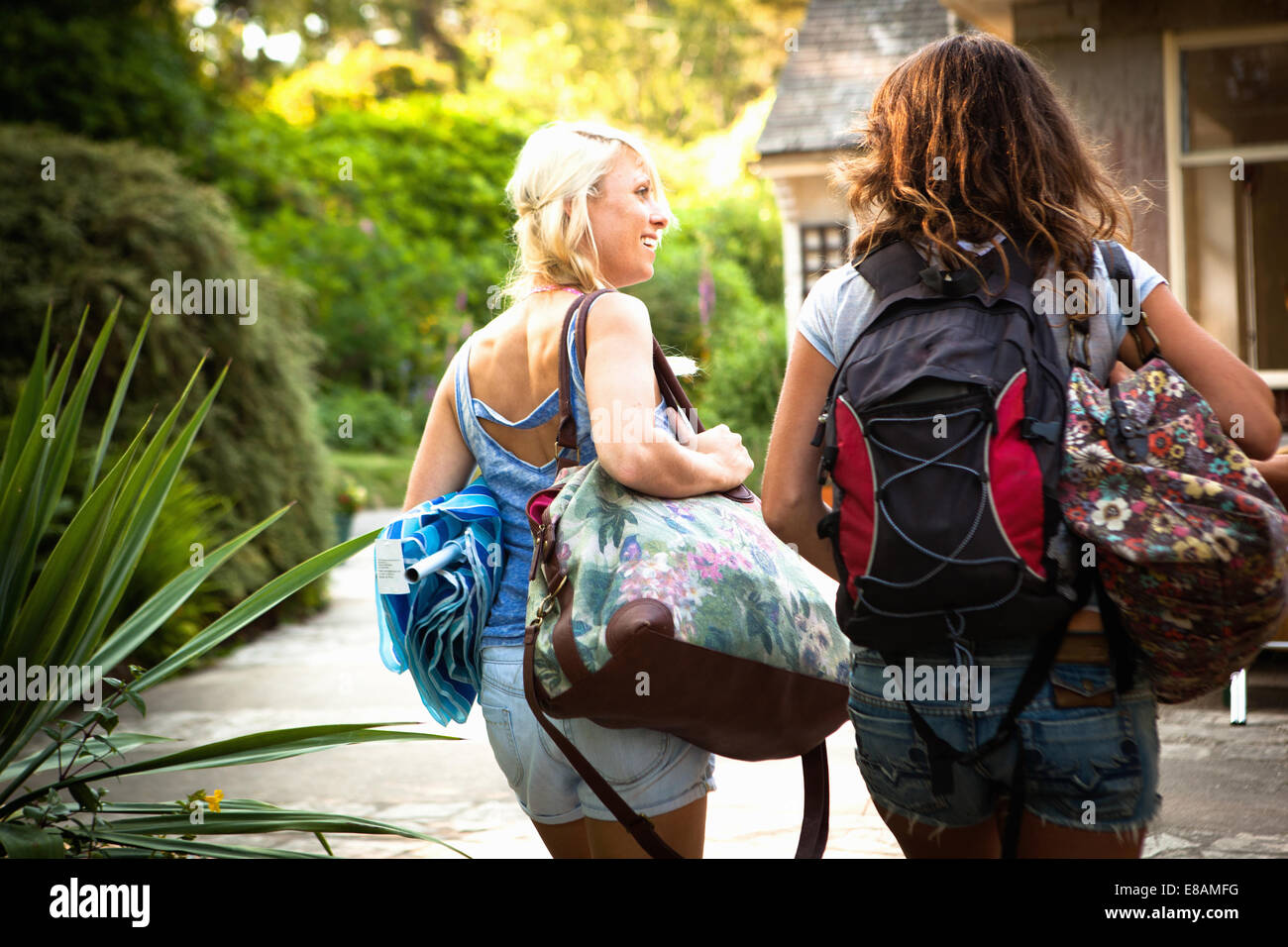 Rear view of two female friends out walking with backpack and bags - Stock Image