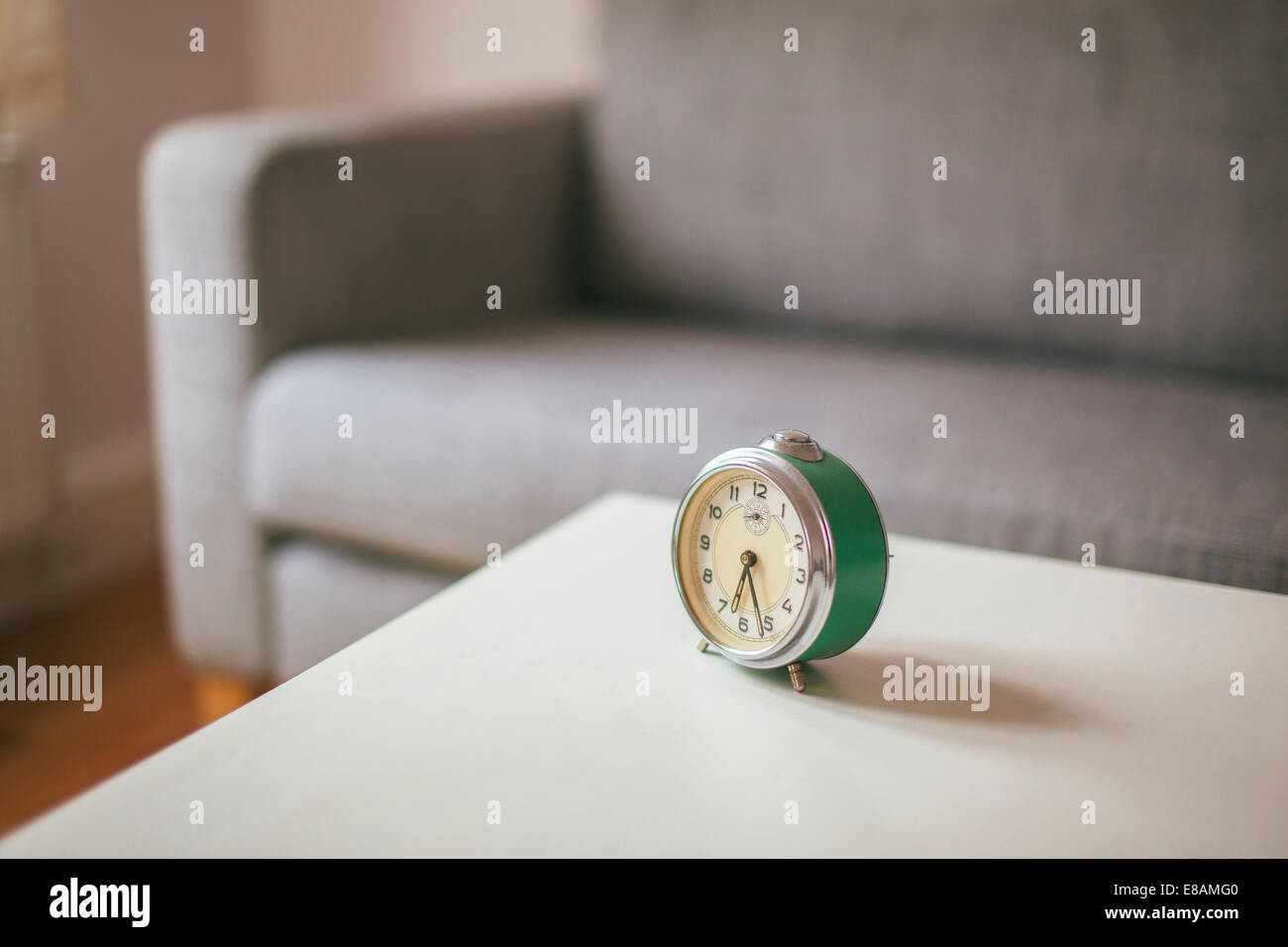 Alarm clock on coffee table in living room - Stock Image