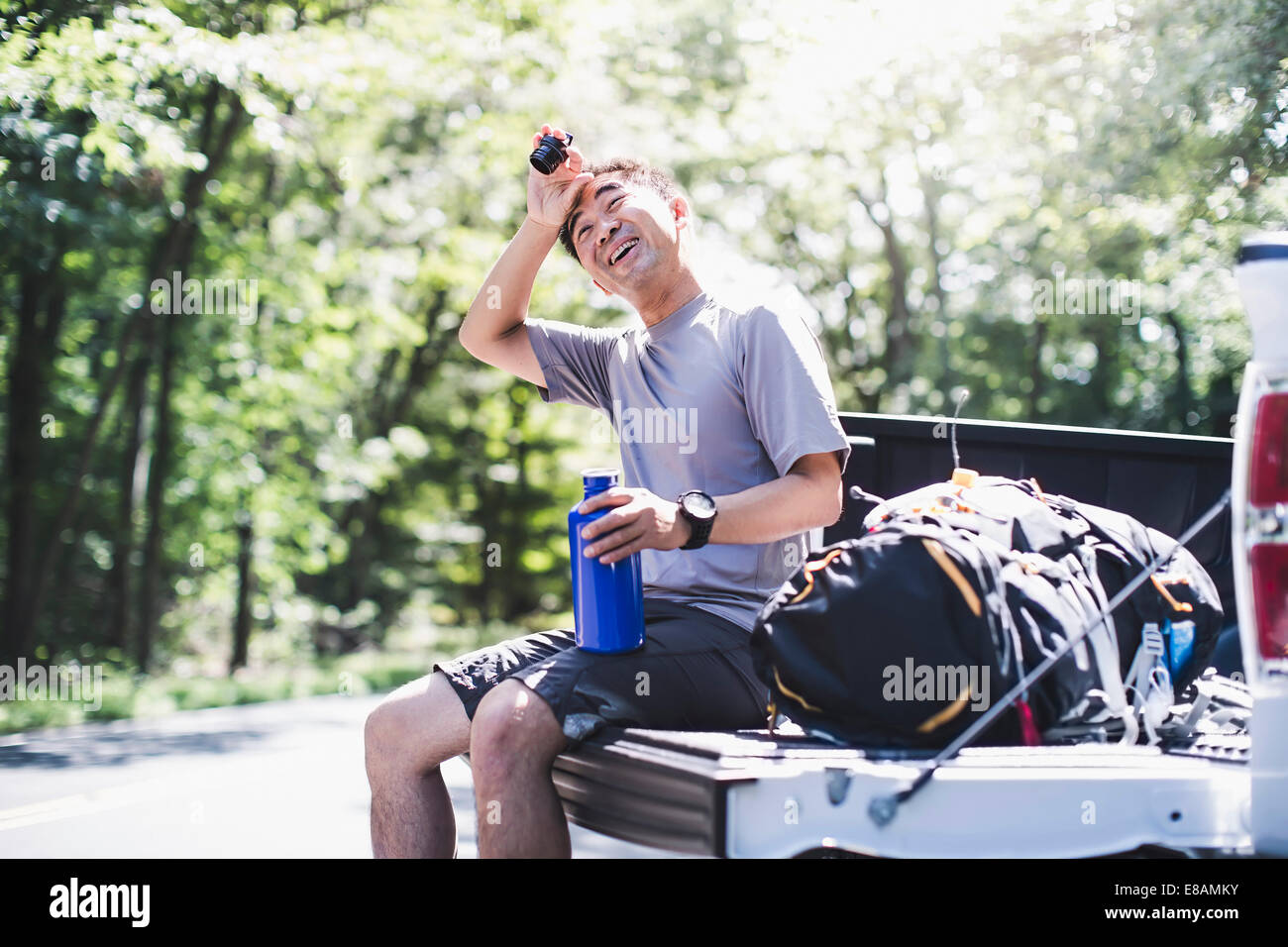 Mature man sitting on pick up truck, wiping brow - Stock Image
