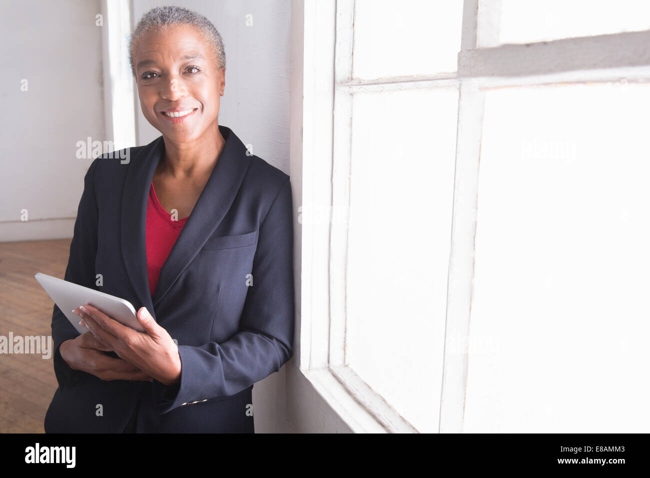 Mature woman holding digital tablet, portrait - Stock Image