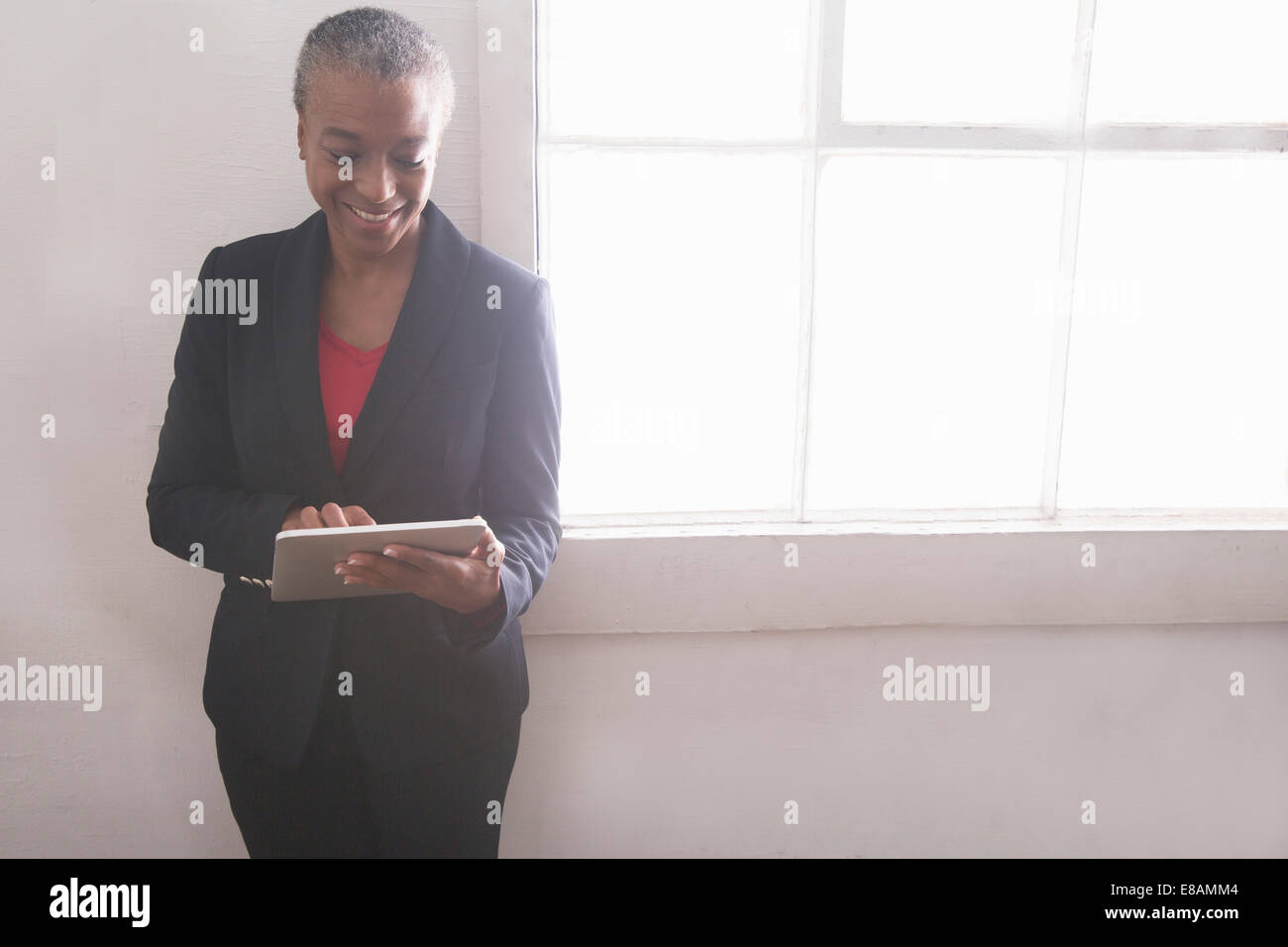 Mature woman using digital tablet, portrait - Stock Image