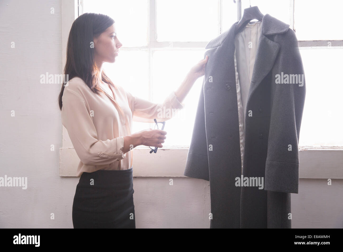 Businesswoman inspecting grey coat - Stock Image