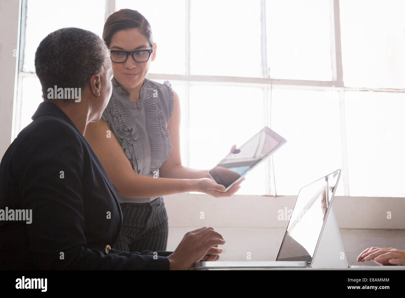Businesswoman showing colleague digital tablet - Stock Image