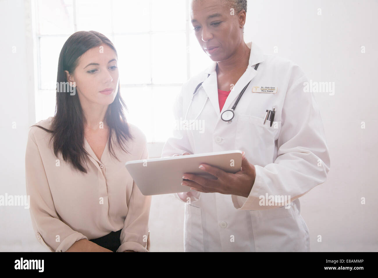 Female doctor using digital tablet in consultation - Stock Image