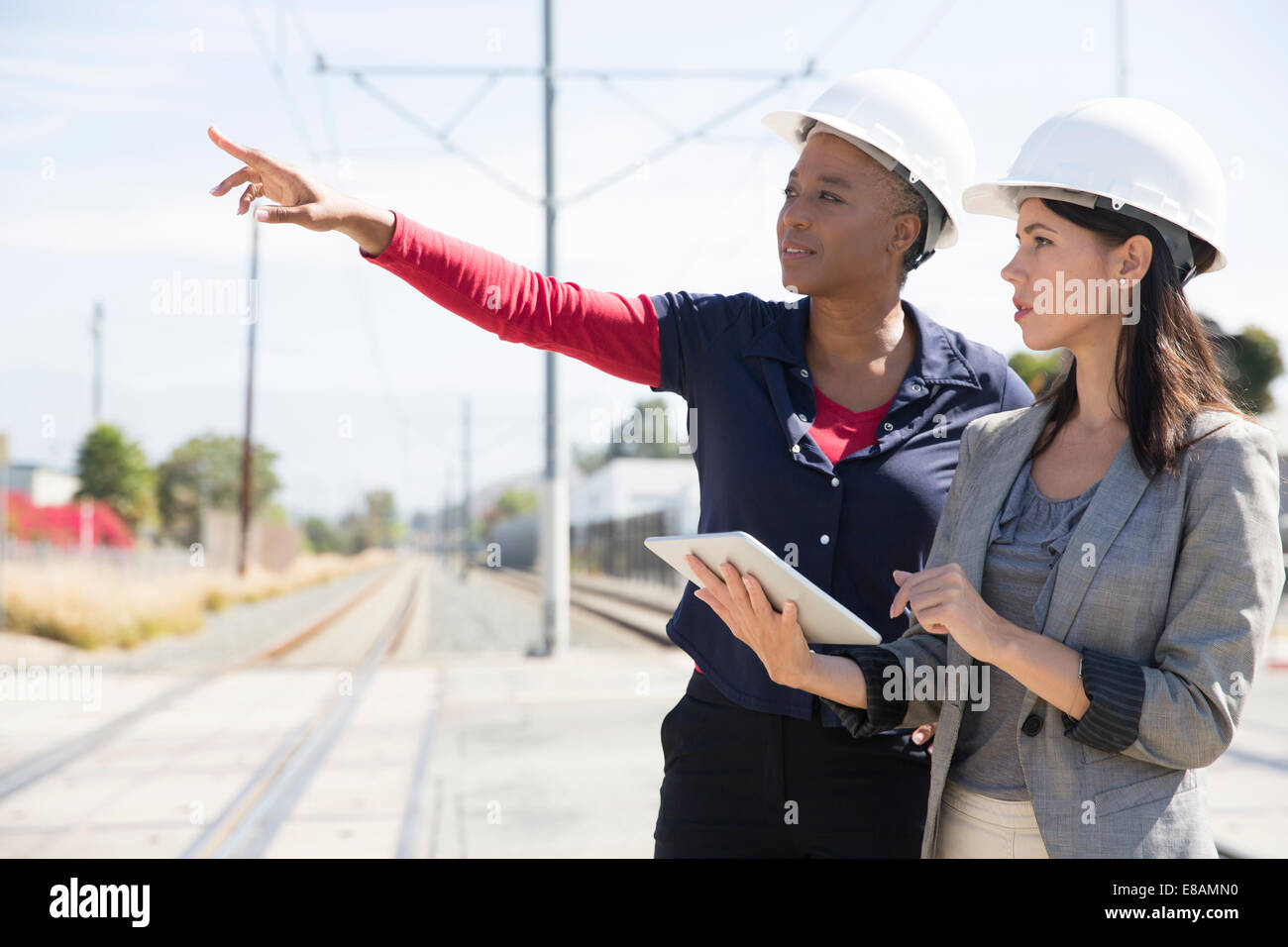 Female architect holding digital tablet, other woman pointing - Stock Image