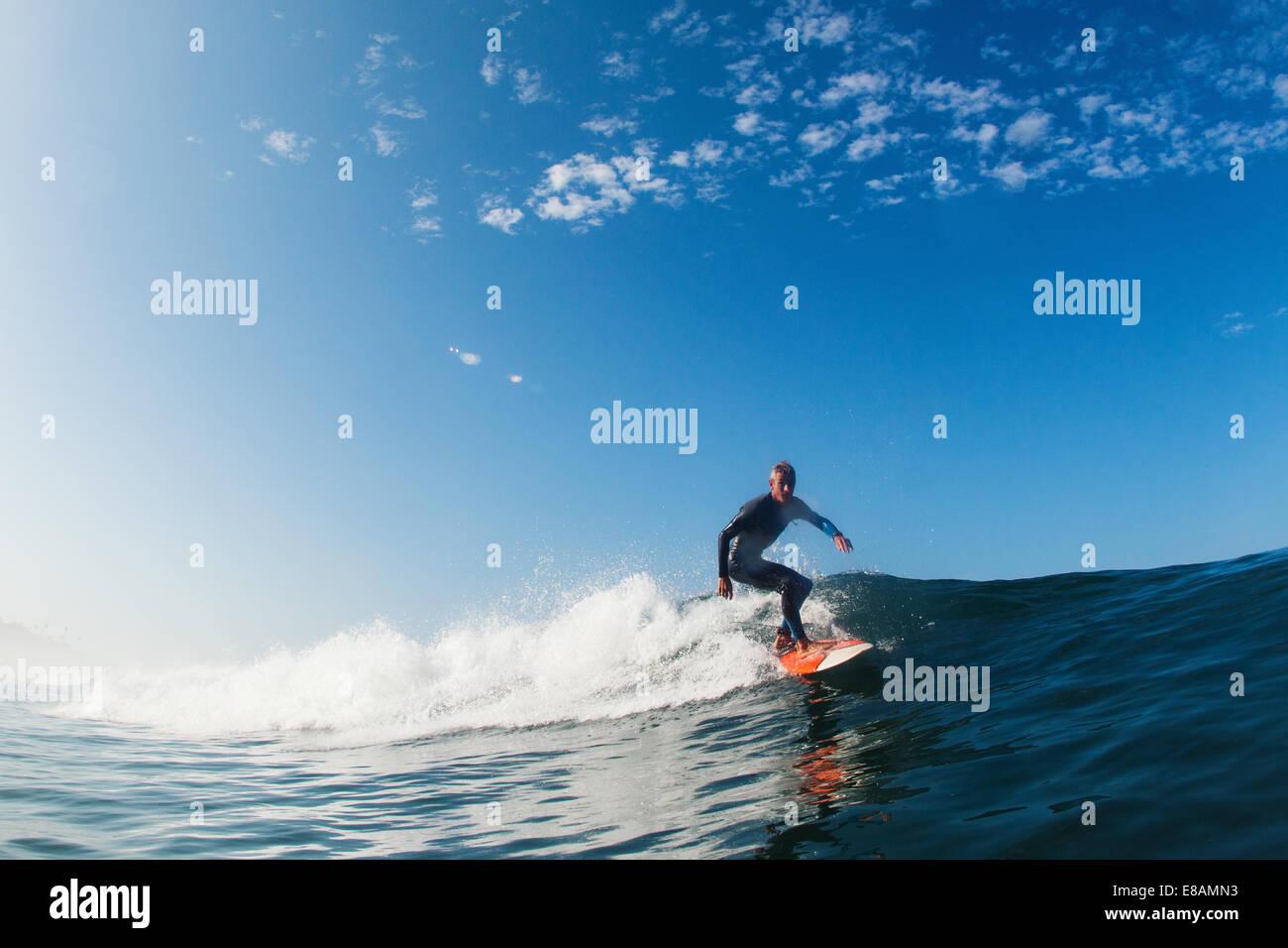 Mid adult man surfing wave, Leucadia, California, USA - Stock Image