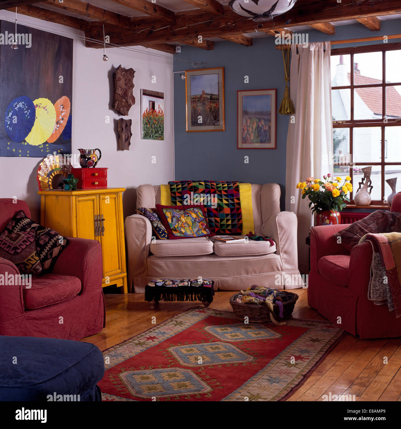 patterned rug in blue and white cottage living room with colourful throws and cushions on the sofa and armchairs - Colourful Living Room
