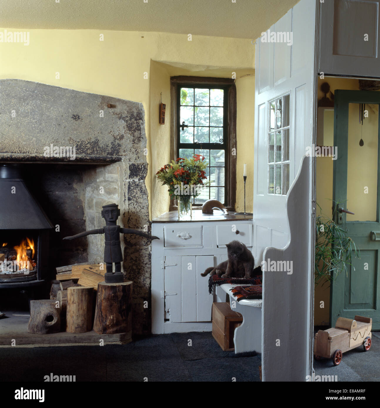 Primitive wooden figure on logs beside wood burning stove in cottage living room with cat sitting on painted seat - Stock Image