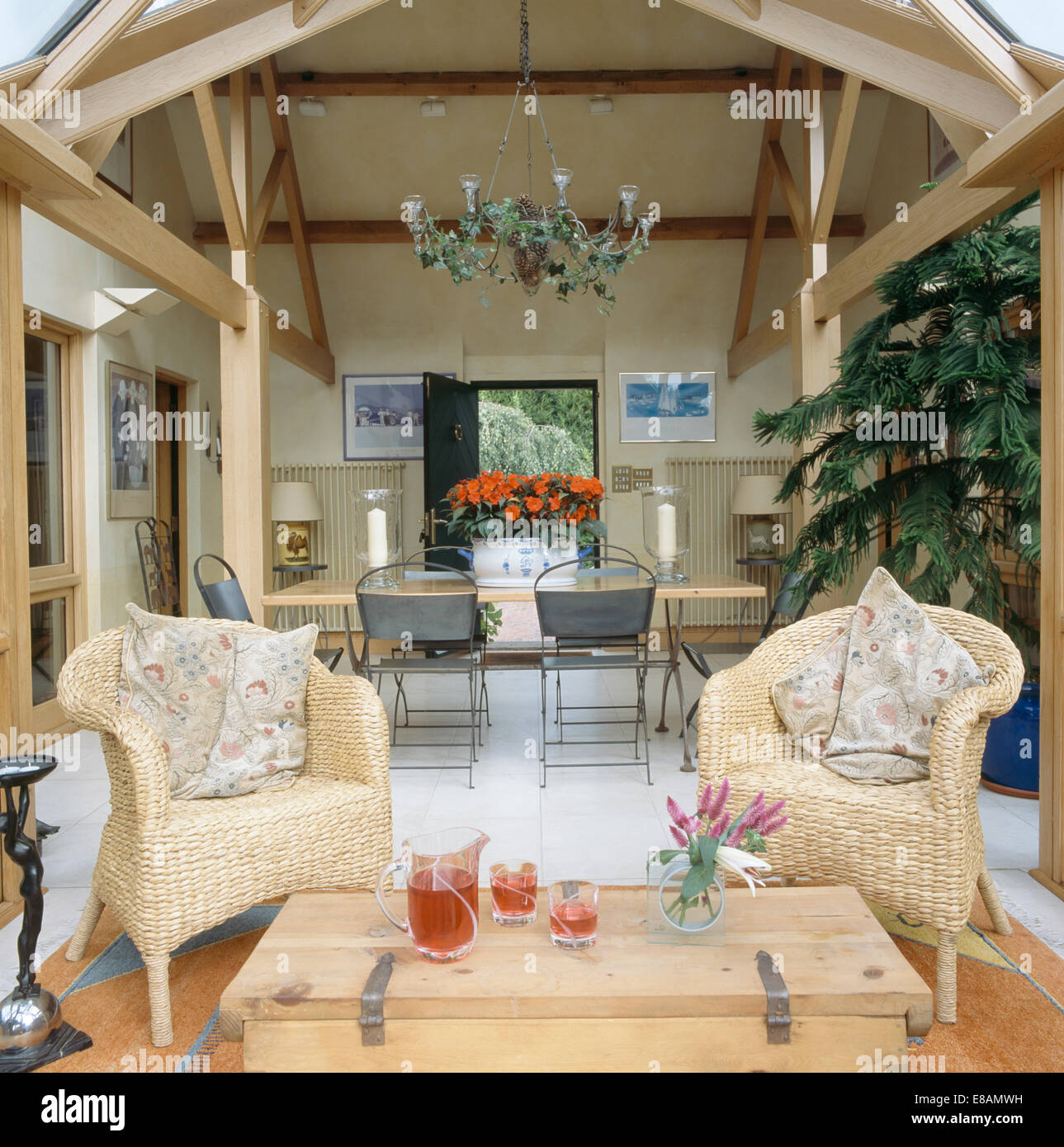 seagrass chairs and pine table in conservatory extension of modern