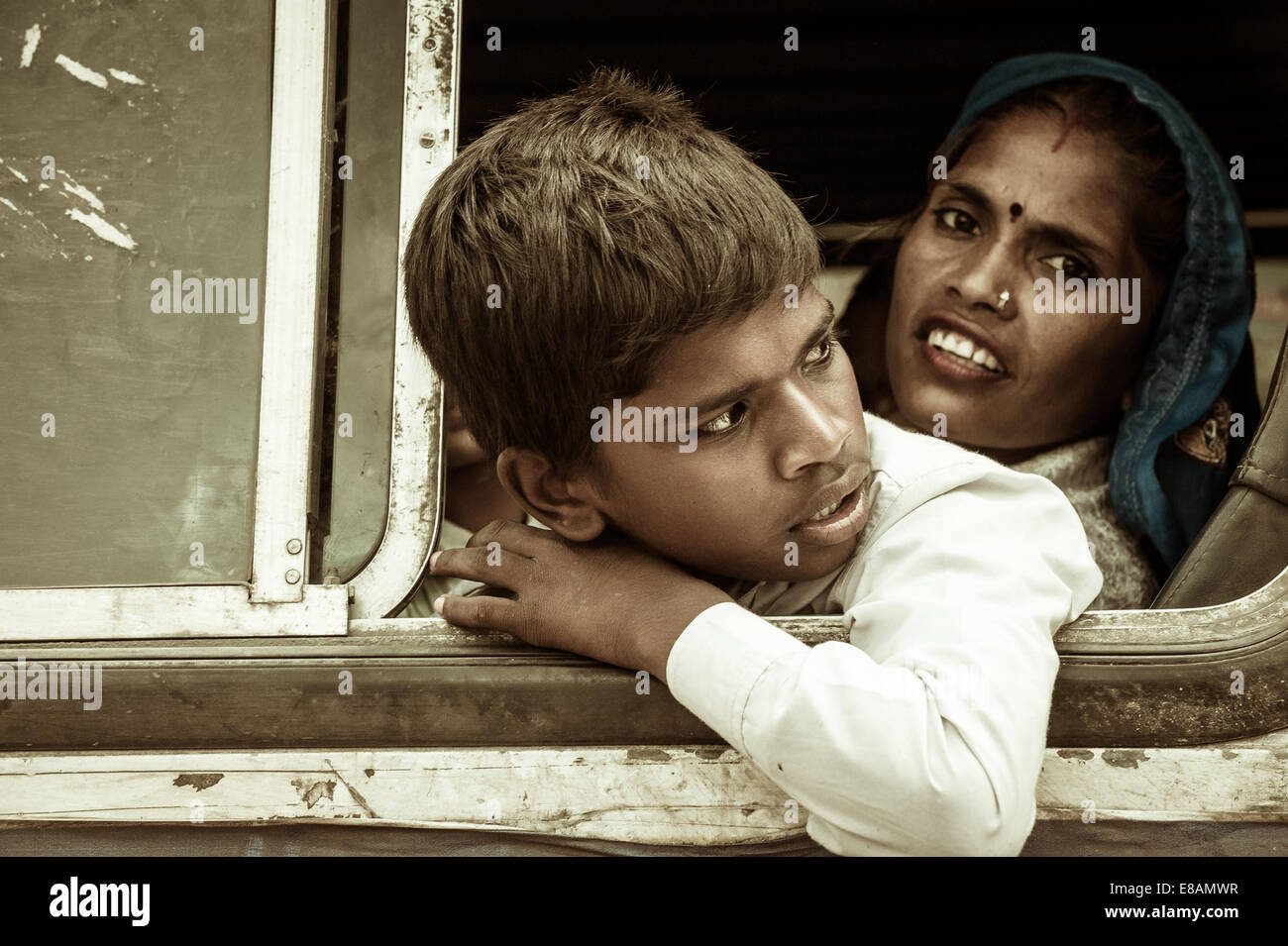 Young Indian traveller with her mother looking outside from a bus window - Stock Image