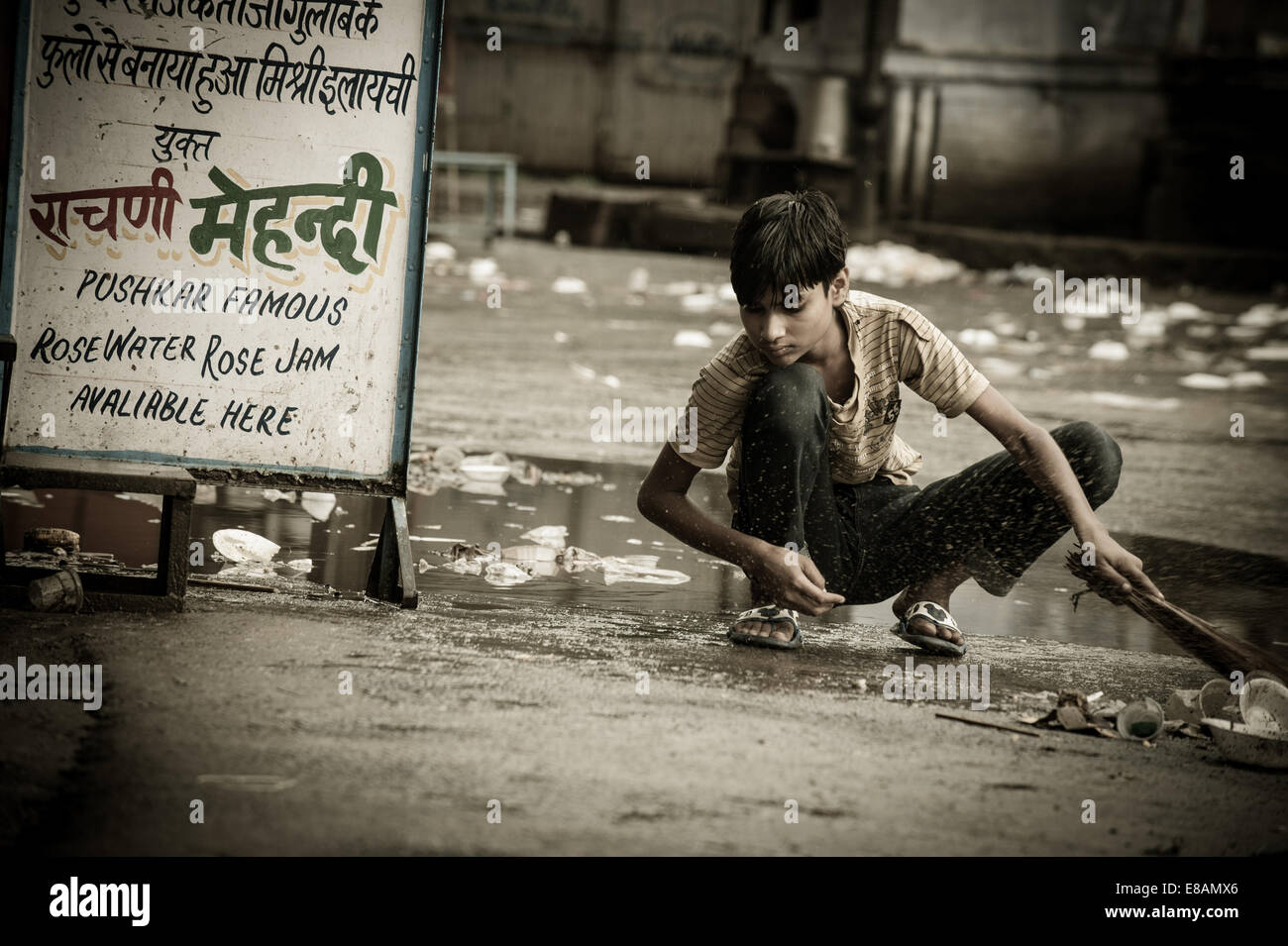 Rural Life in Rajasthan, young boy cleaning the street - Stock Image