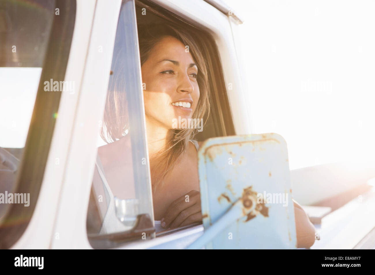 Young female surfer looking out of pick up truck window, Leucadia, California, USA - Stock Image