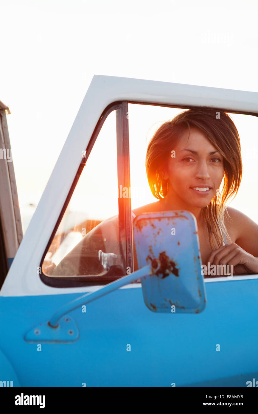 Portrait of young female surfer through pick up truck window, Leucadia, California, USA - Stock Image