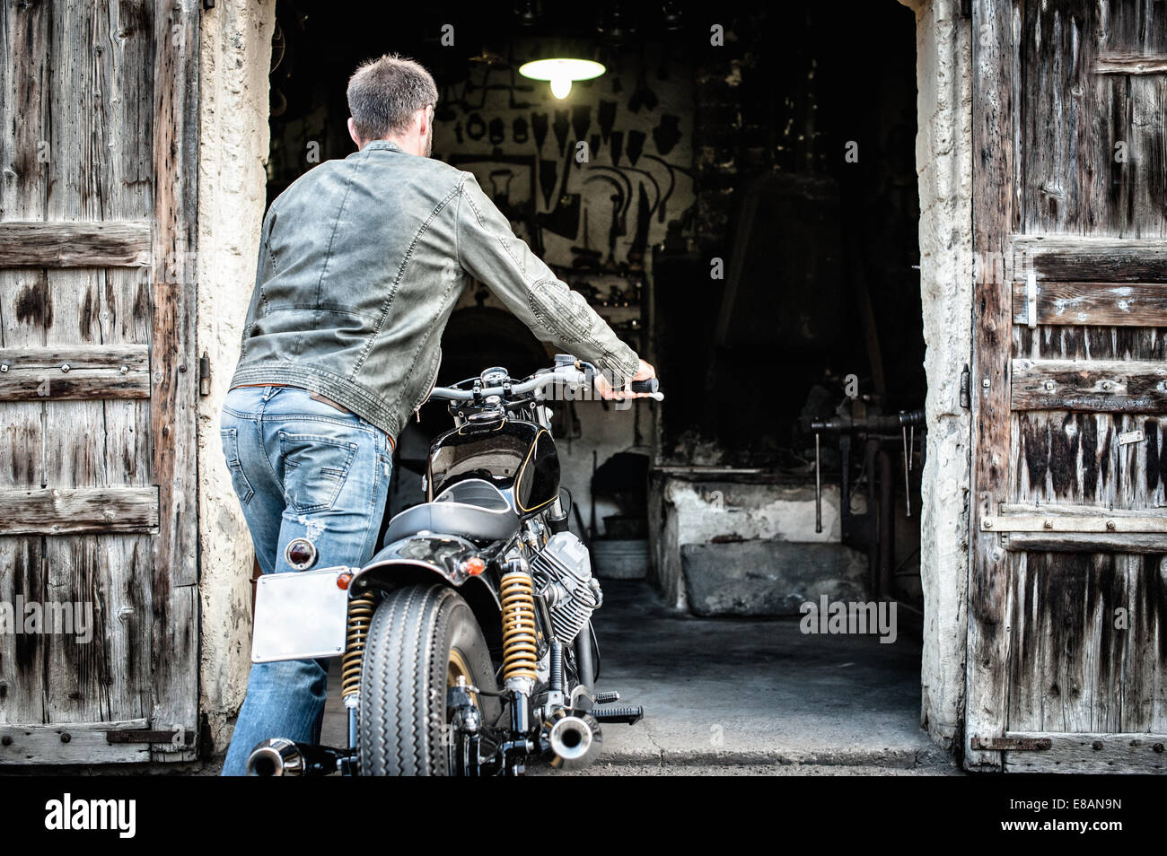 Mid adult man pushing motorcycle into barn - Stock Image