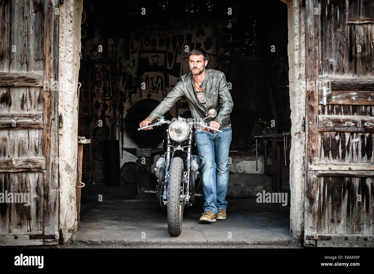Mid adult man pushing motorcycle out of barn doorway - Stock Image