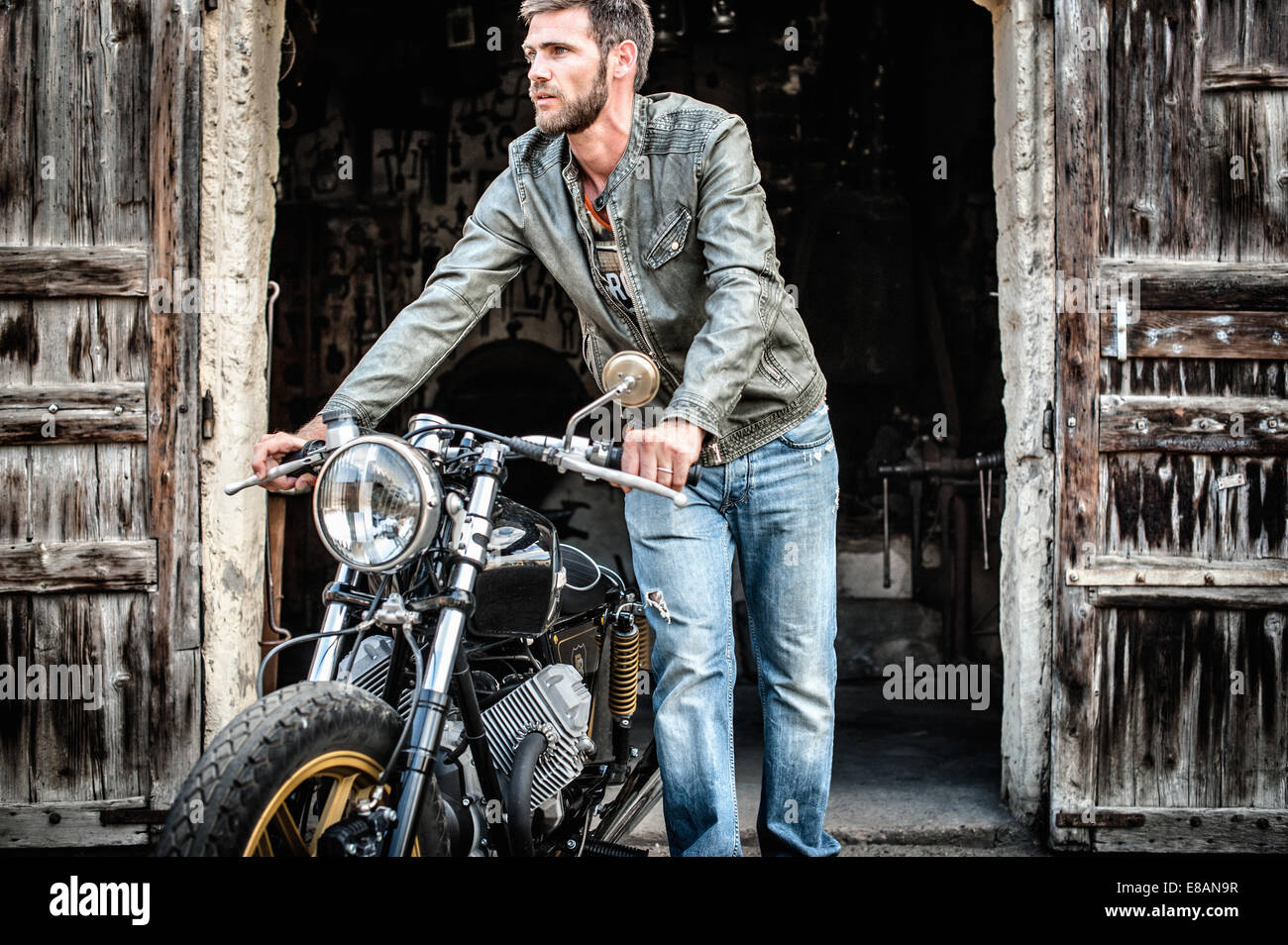 Mid adult man pushing motorcycle out of barn - Stock Image