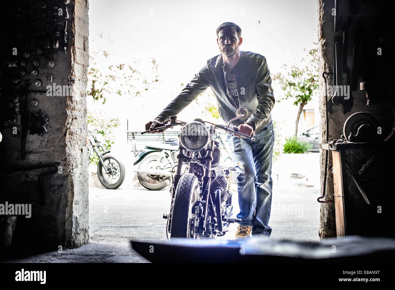 Mid adult man pushing motorcycle through barn doorway - Stock Image