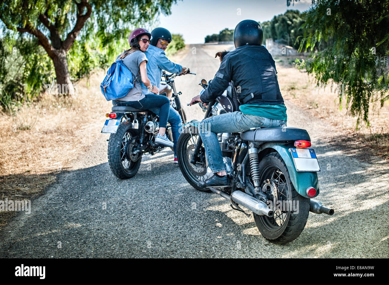 Three friends and one dog on motorcycles, Cagliari, Sardinia, Italy - Stock Image
