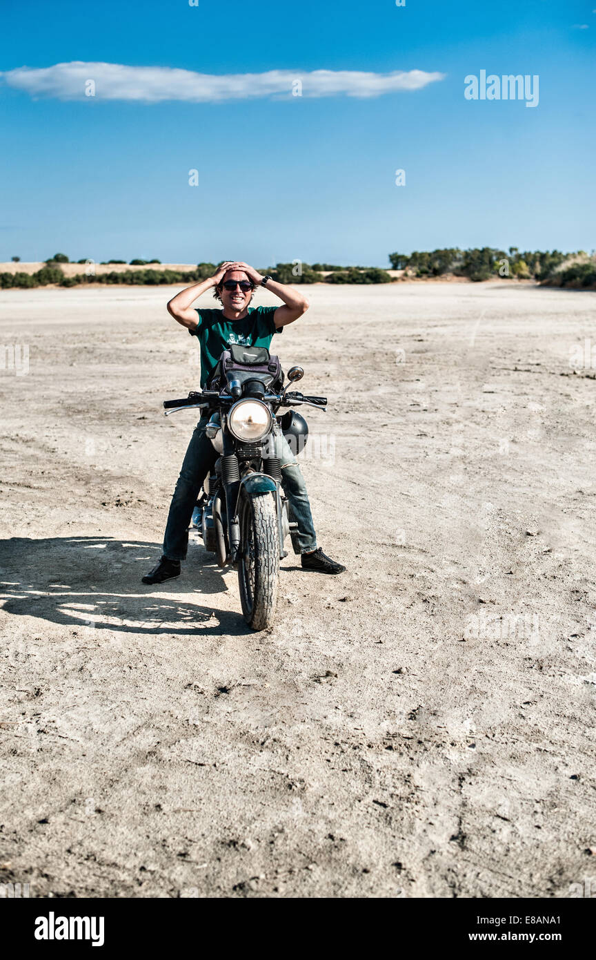 Mid adult man sitting on motorcycle on arid plain, Cagliari, Sardinia, Italy - Stock Image