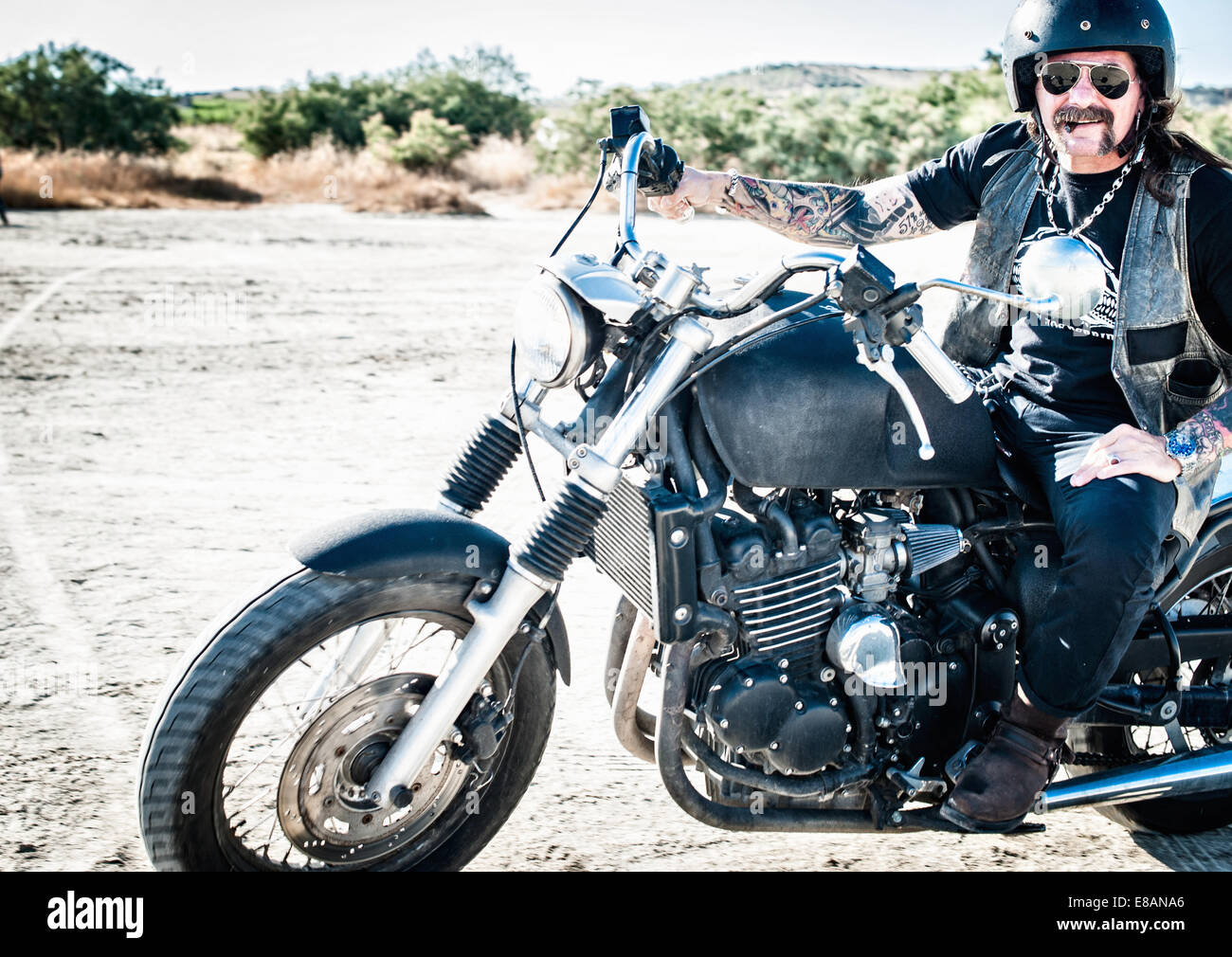 Portrait of male motorcyclist on arid plain, Cagliari, Sardinia, Italy - Stock Image