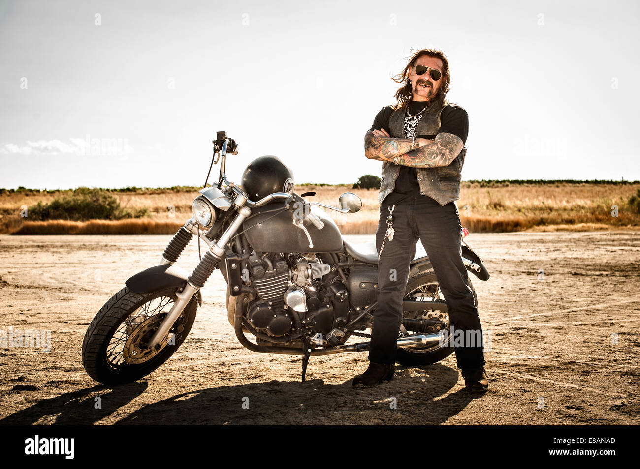 Portrait of mature male motorcyclist on arid plain, Cagliari, Sardinia, Italy - Stock Image