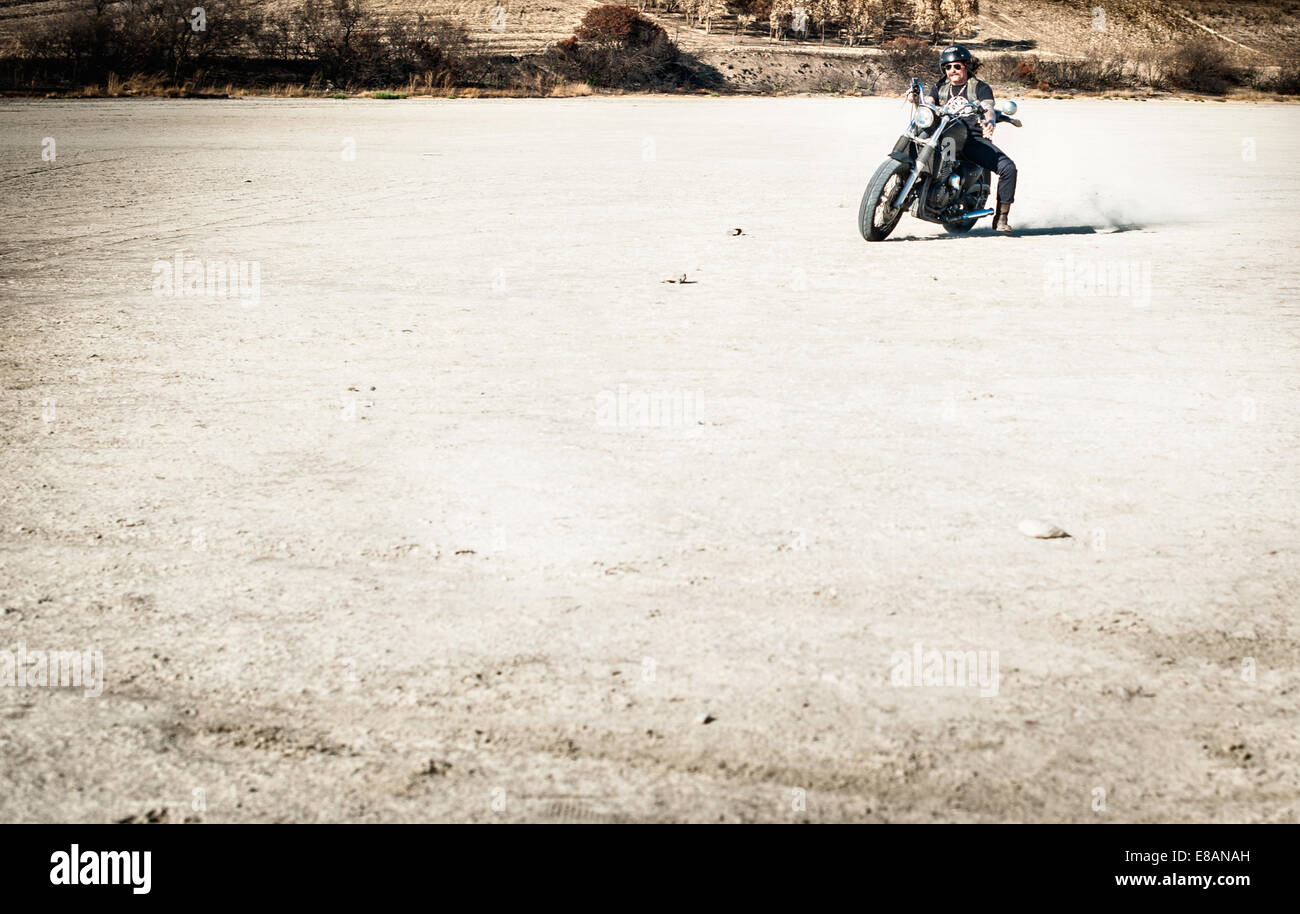 Mature man riding motorcycle on arid plain, Cagliari, Sardinia, Italy - Stock Image
