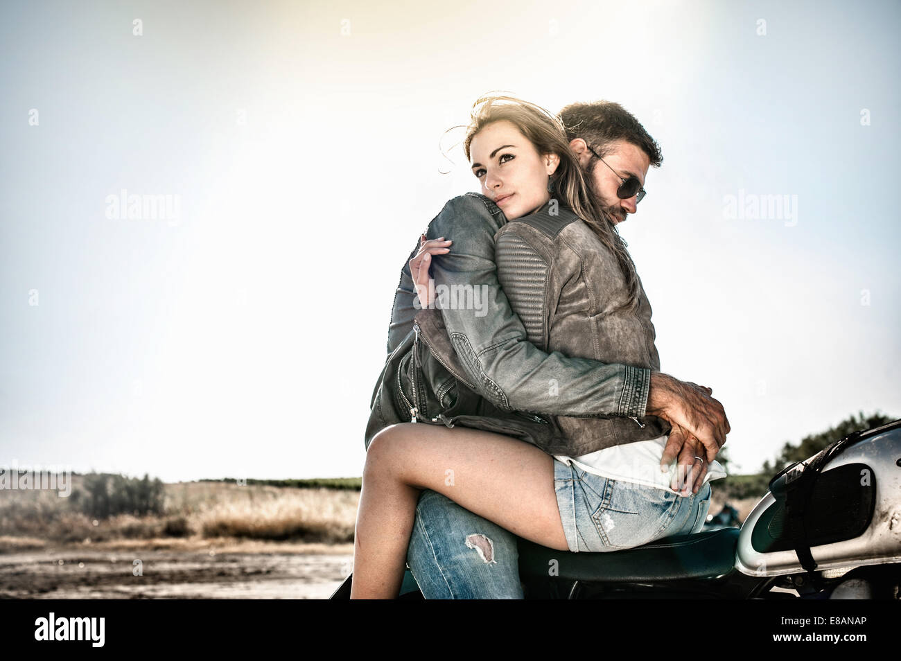 Young couple hugging and straddling motorcycle on arid plain, Cagliari, Sardinia, Italy - Stock Image