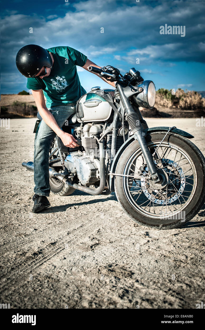 Mid adult man checking motorcycle on arid plain, Cagliari, Sardinia, Italy - Stock Image