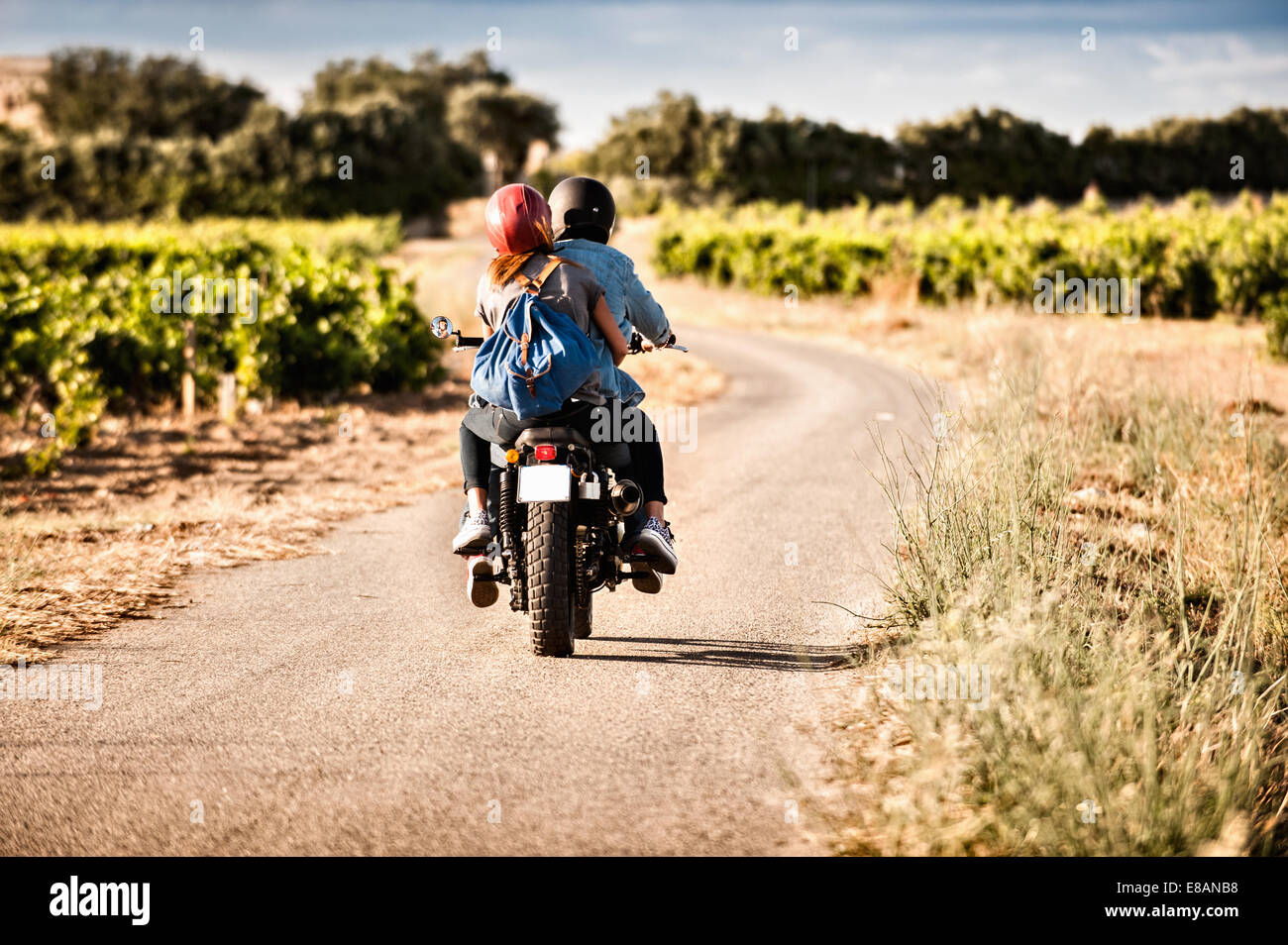 Rear view of mid adult couple riding motorcycle on winding rural road, Cagliari, Sardinia, Italy - Stock Image