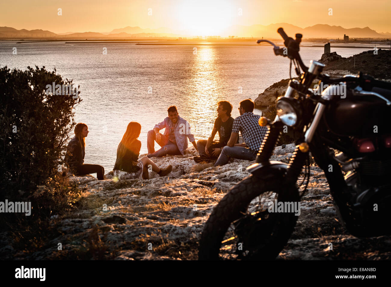 Five motorcycling friends taking a break on coast at sunset, Cagliari, Sardinia, Italy - Stock Image
