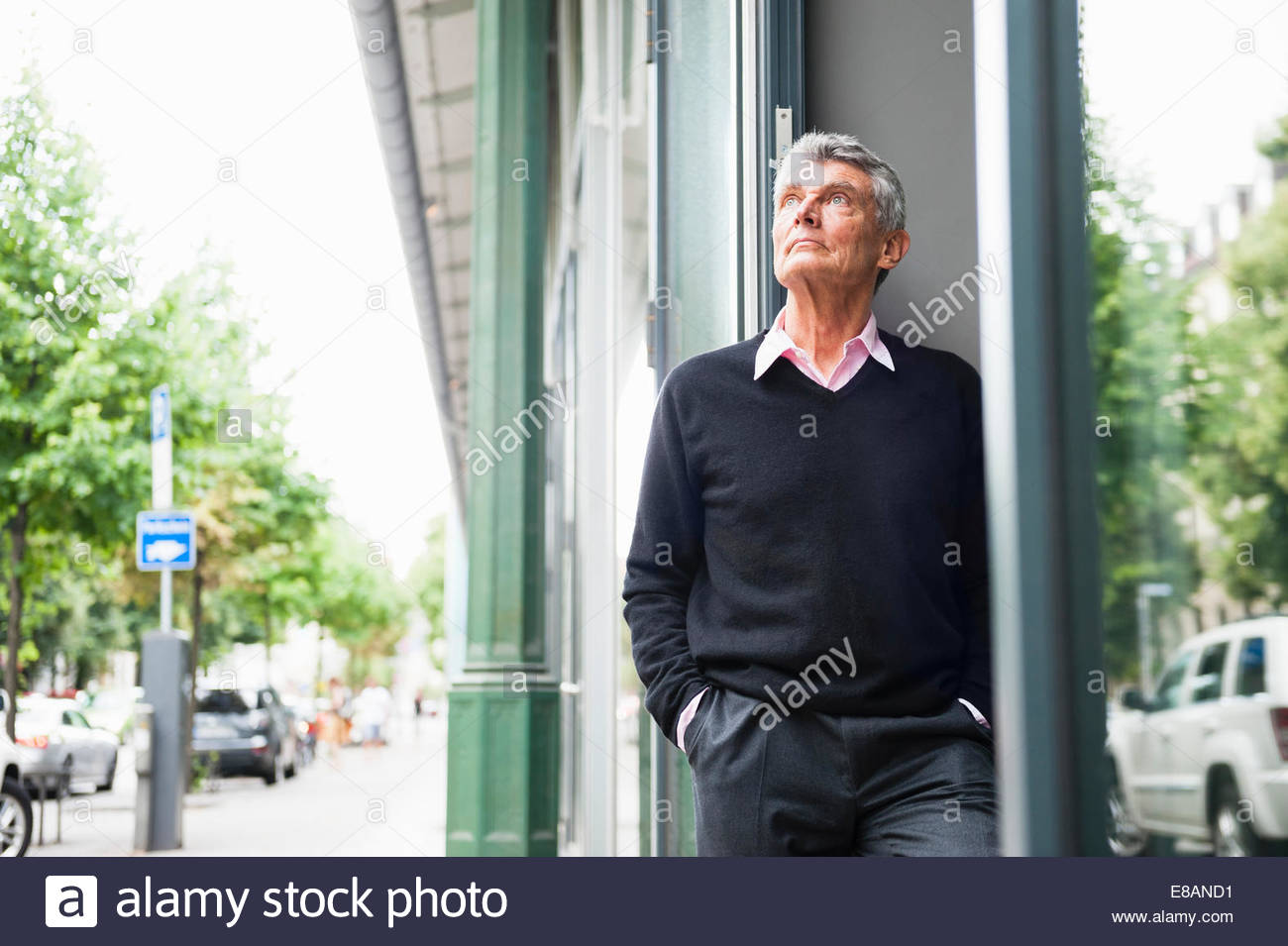 Sad senior man looking up from city street - Stock Image