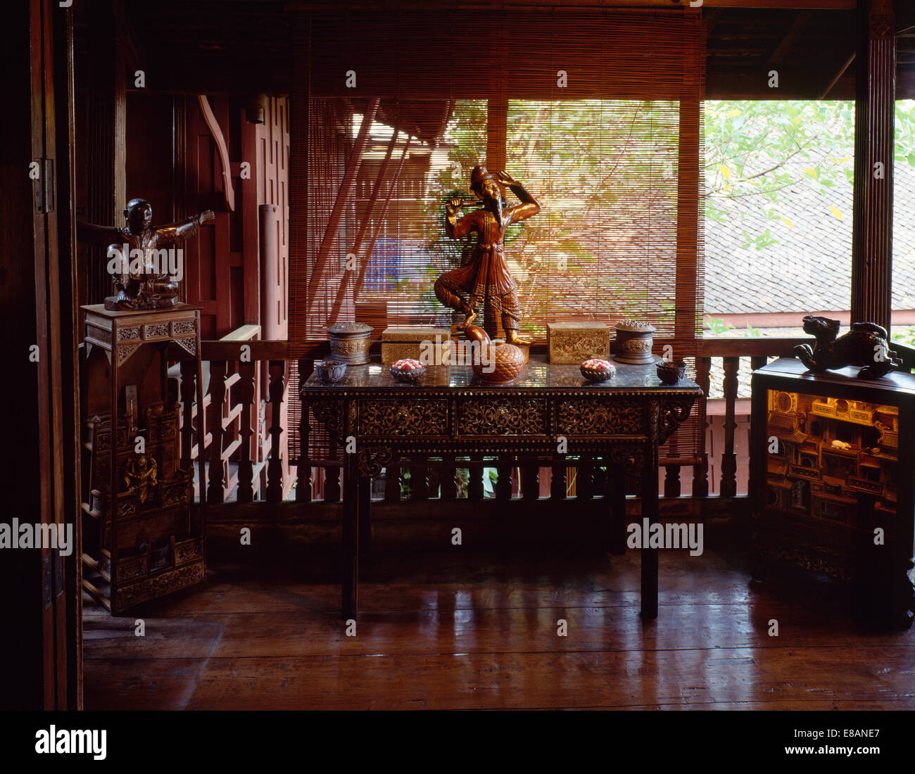 Asian statue on carved wood table on veranda with polished wood floor and split cane blinds - Stock Image