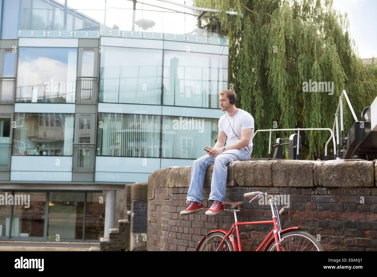 Man listening to music by canal, East London, UK - Stock Image