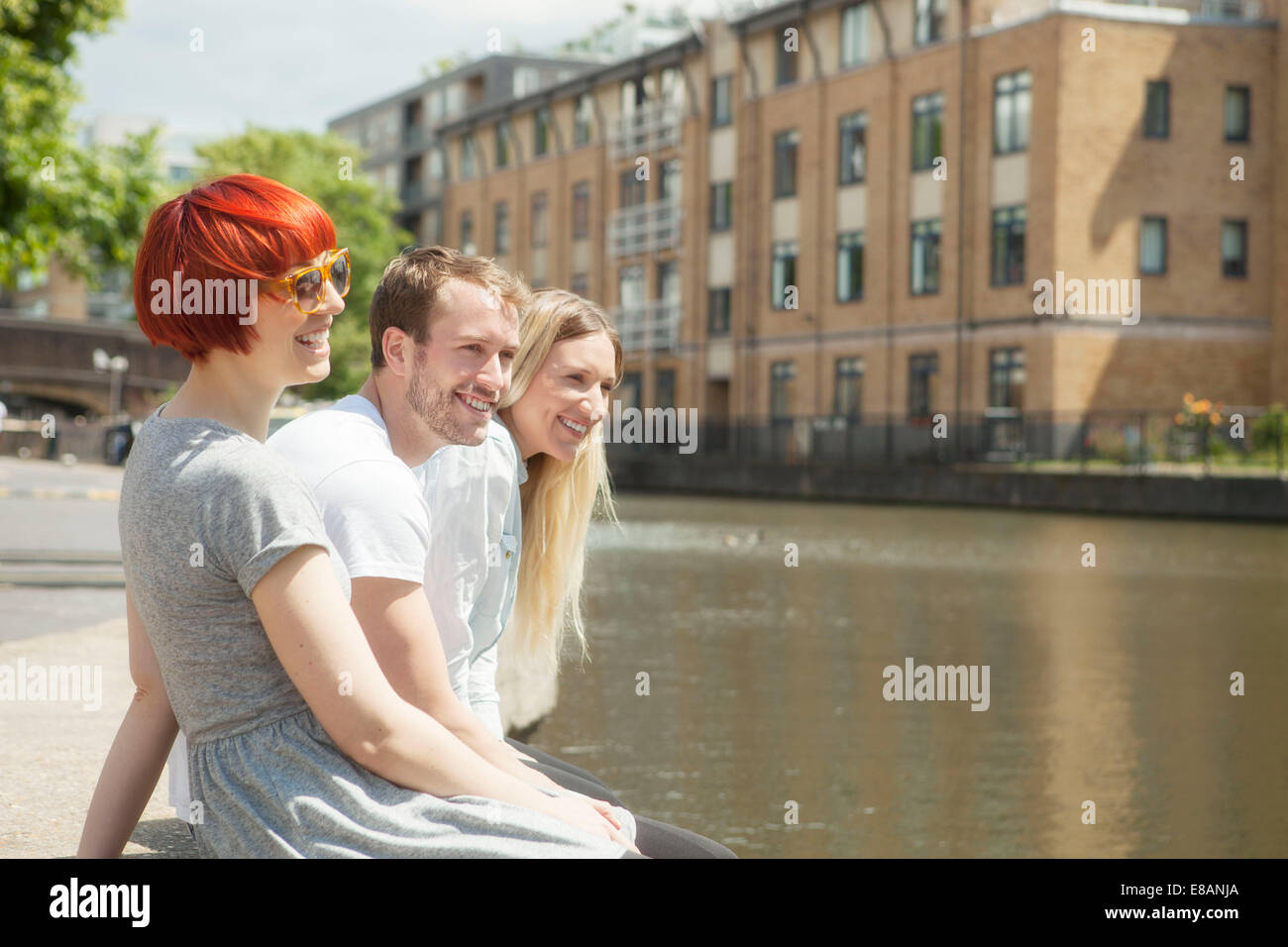 Friends sitting on canal side, East London, UK - Stock Image