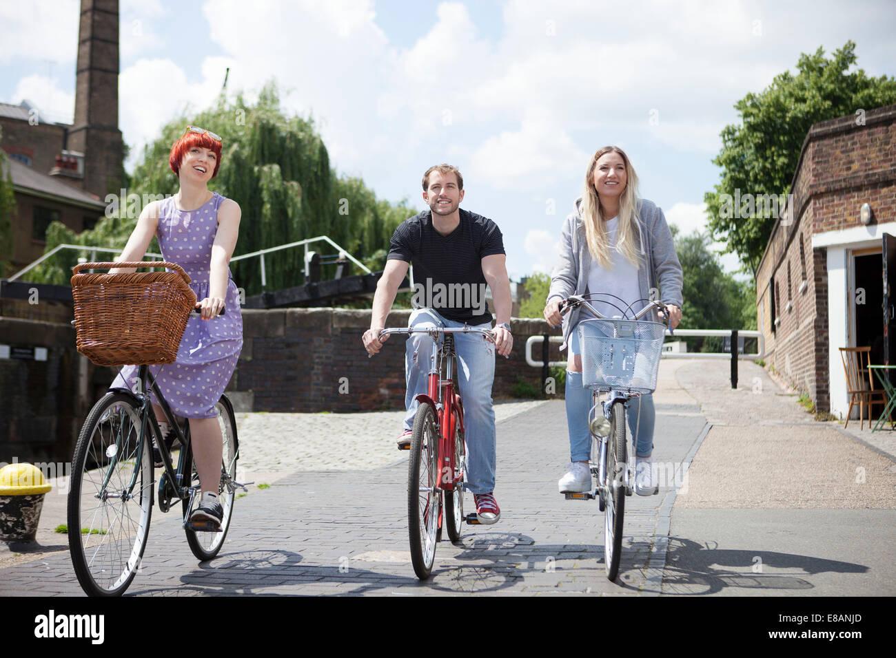 Friends riding bike along canal, East London, UK - Stock Image