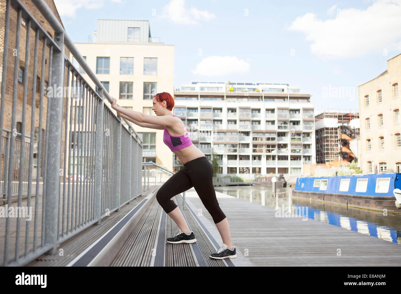 Woman doing stretching exercise, building in background, East London, UK - Stock Image