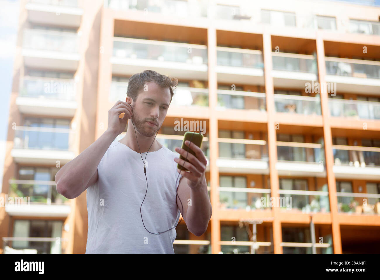 Man listening to music on headphones, building in background - Stock Image