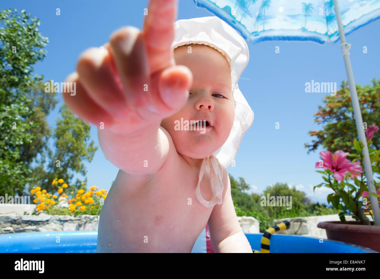 Baby girl in swimming pool pointing finger - Stock Image