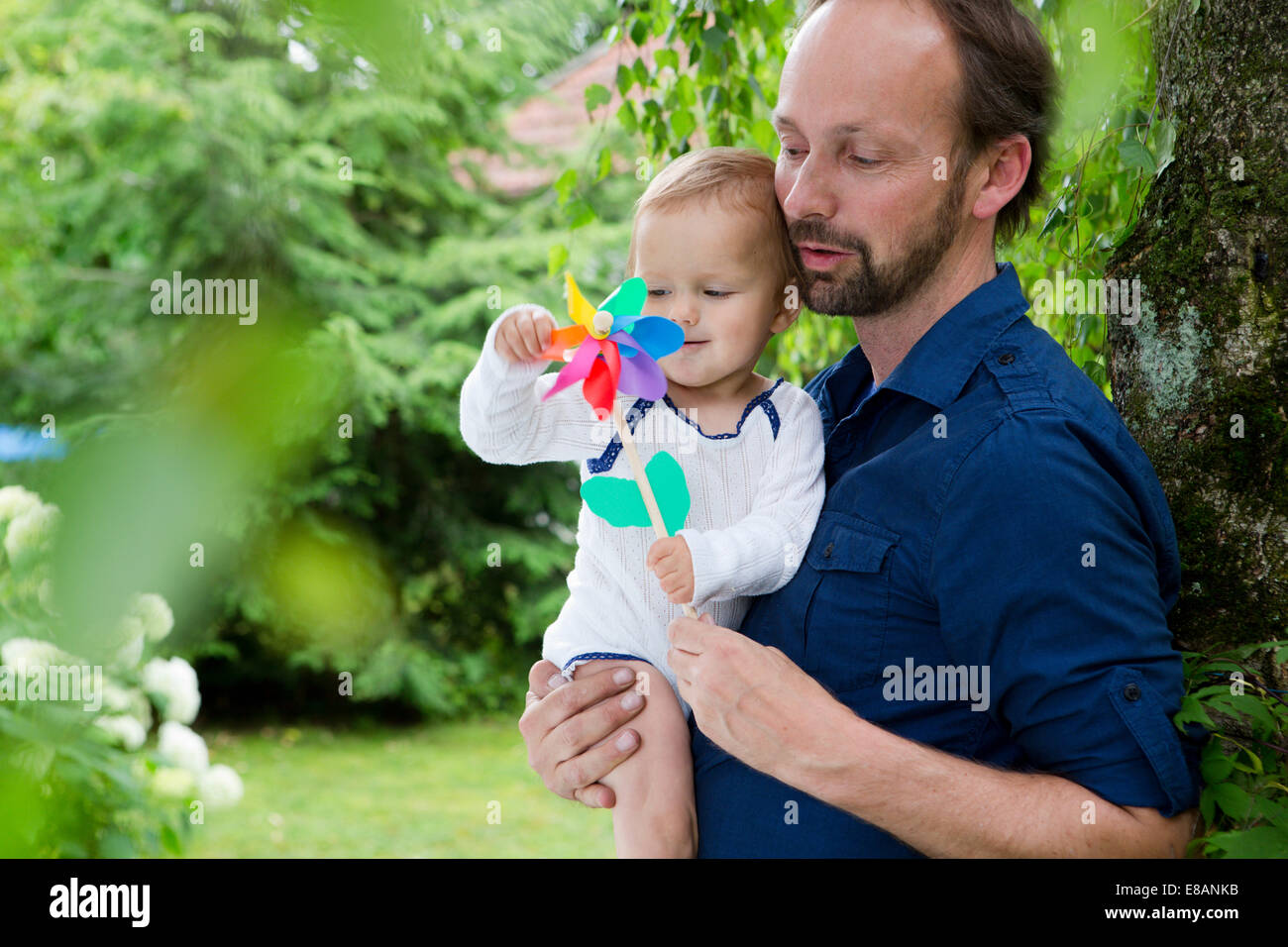 Father and baby daughter playing with pinwheel in garden - Stock Image