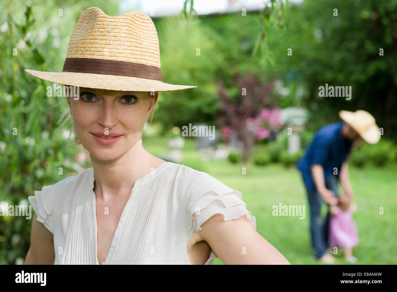 Portrait of mid adult woman in front of family in garden - Stock Image