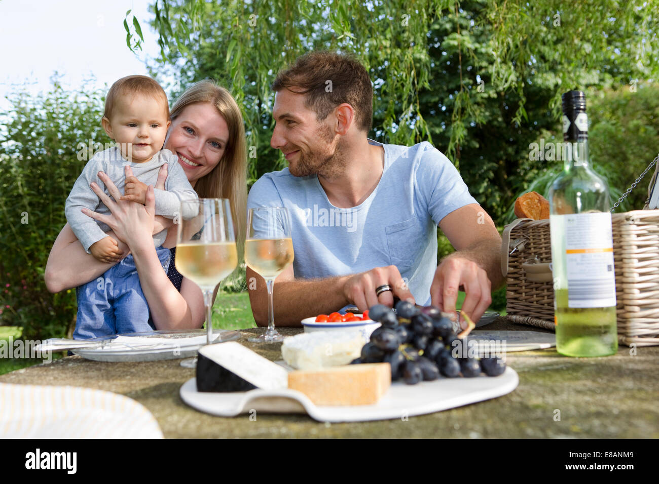 Mid adult couple and baby daughter sitting at picnic table in garden - Stock Image