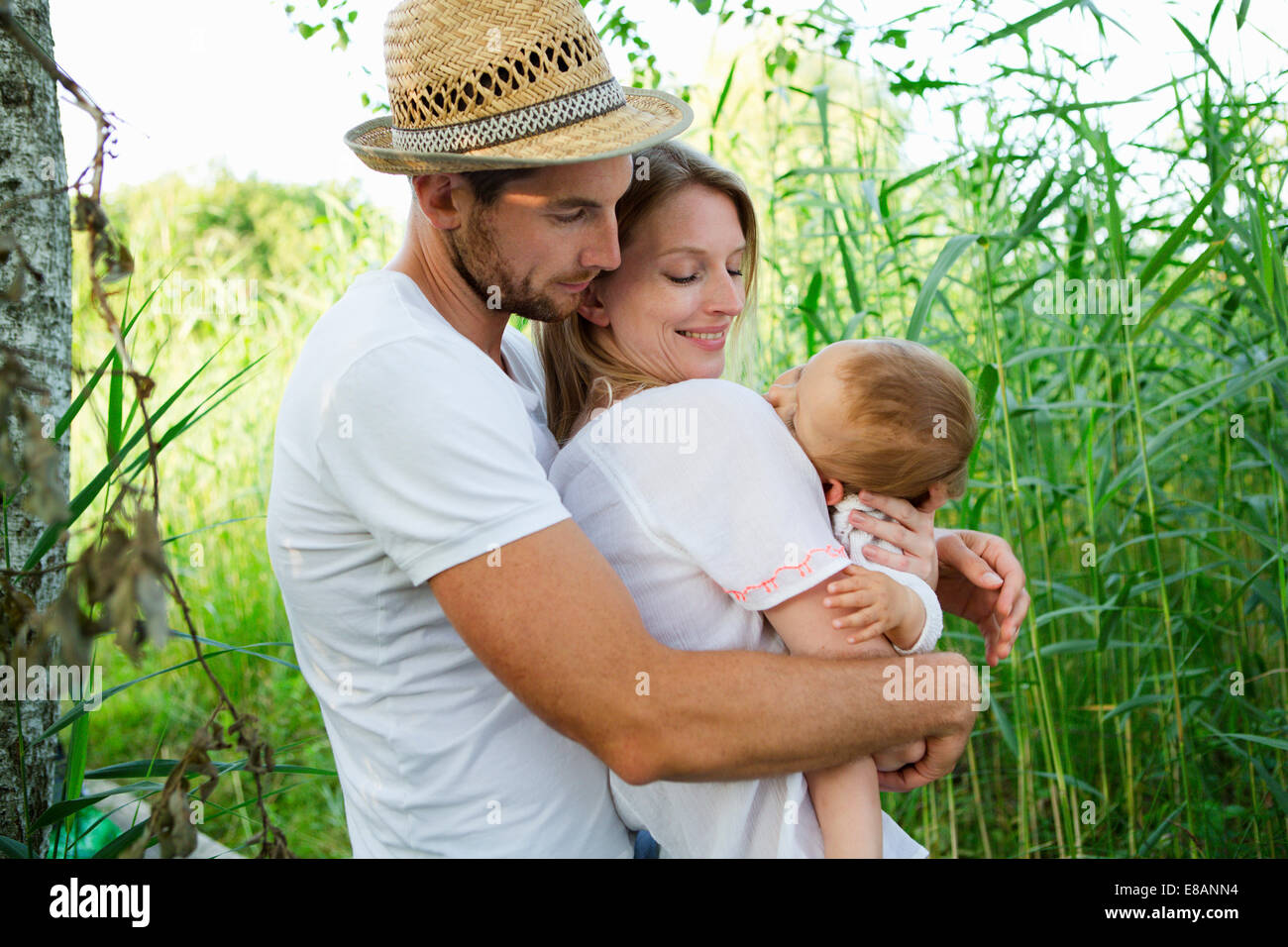 Mid adult couple and baby daughter with arms around each other in reeds - Stock Image