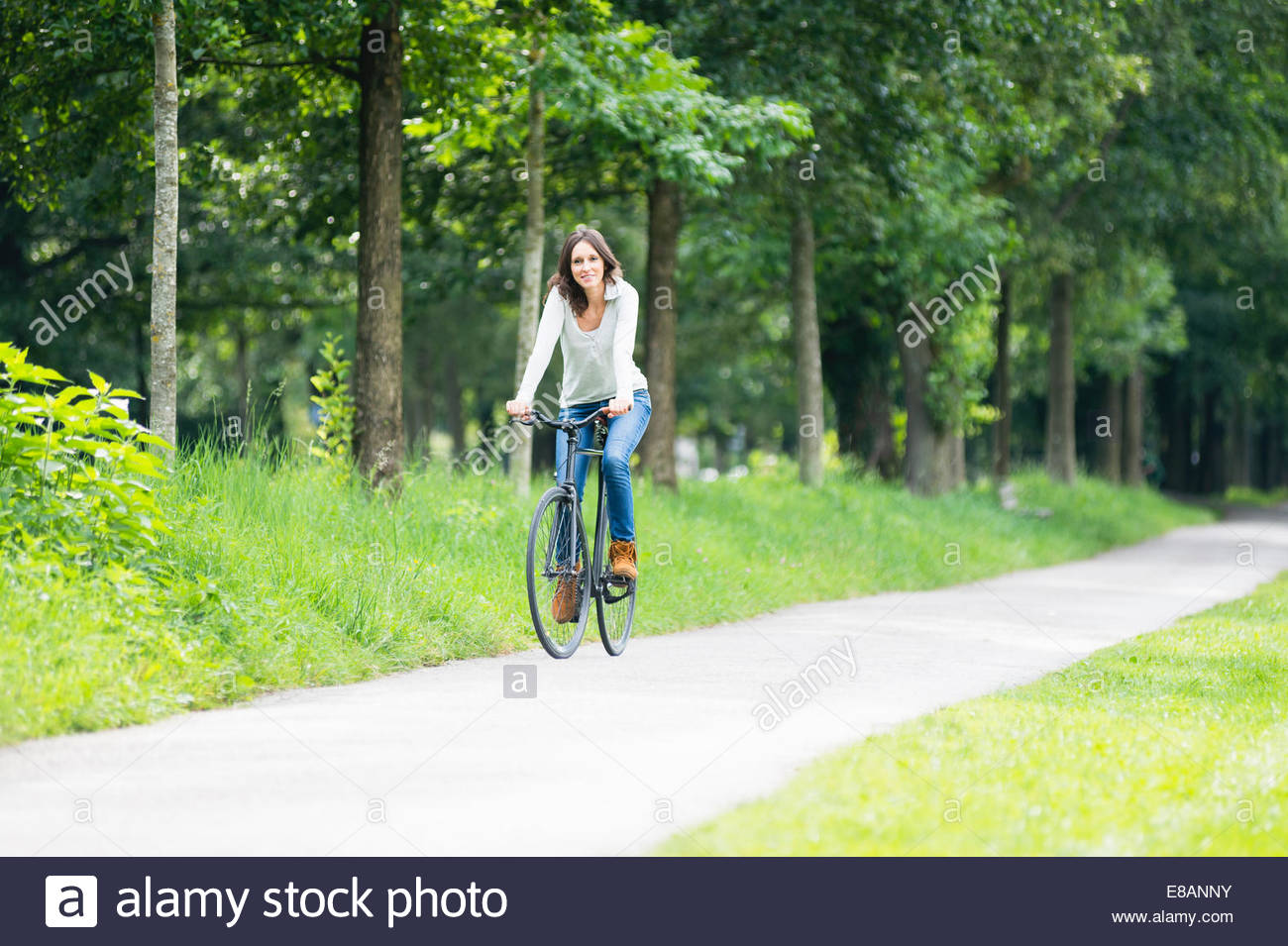 Mid adult woman cycling on park pathway - Stock Image