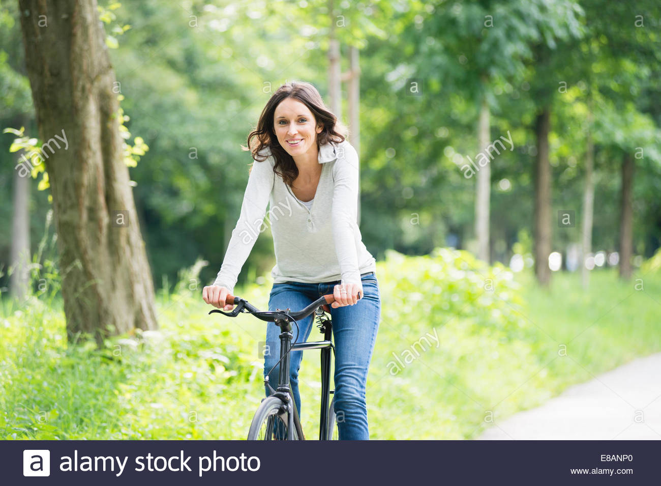 Portrait of mid adult woman cycling in park - Stock Image