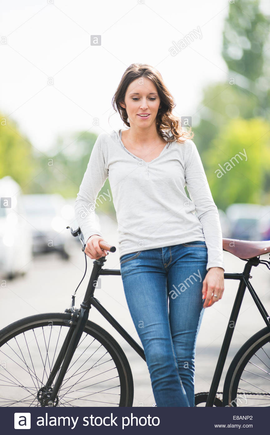 Portrait of mid adult woman leaning against bicycle on street Stock Photo