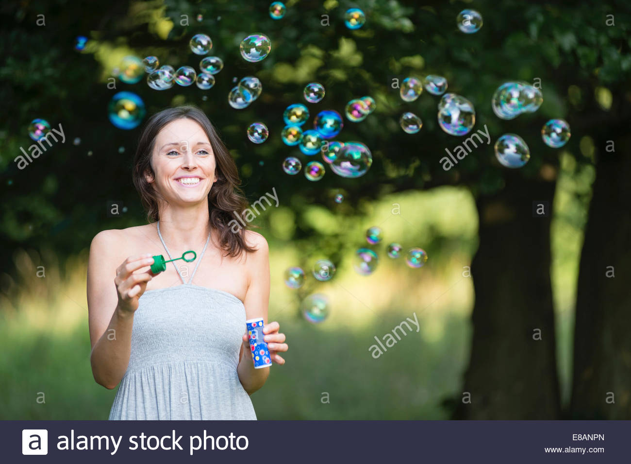 Mid adult woman blowing bubbles in woodland Stock Photo