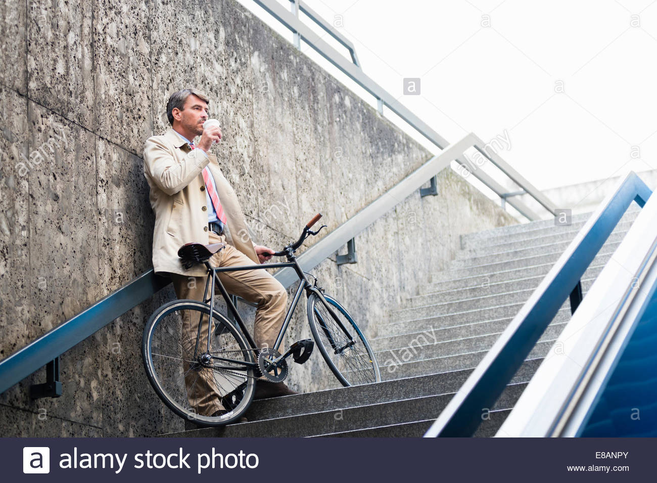 Mature businessman on subway steps drinking takeaway coffee - Stock Image