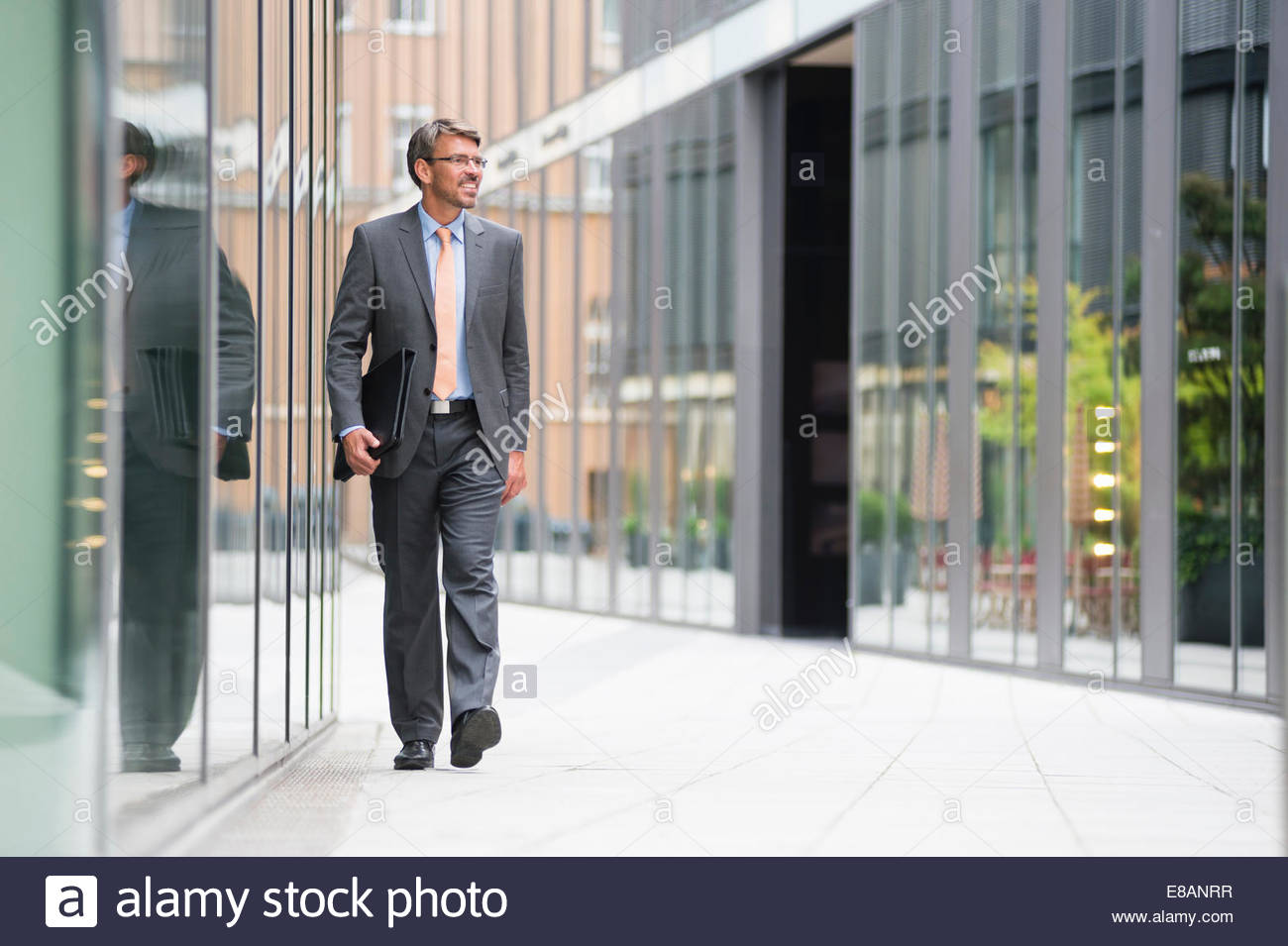Mature businessman walking outside office building - Stock Image