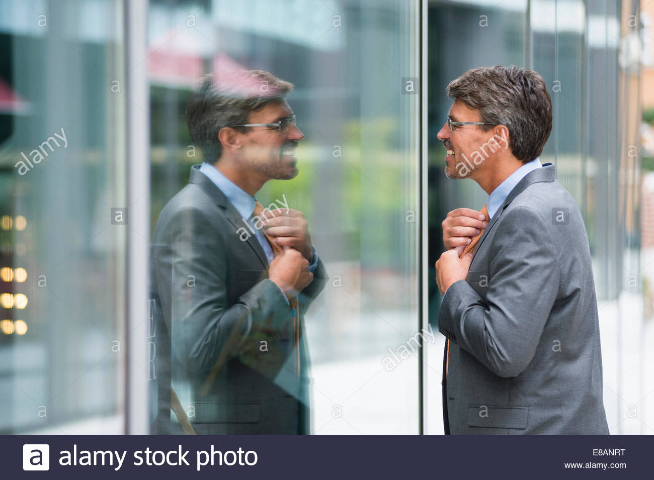 Mature businessman adjusting tie in shop window - Stock Image
